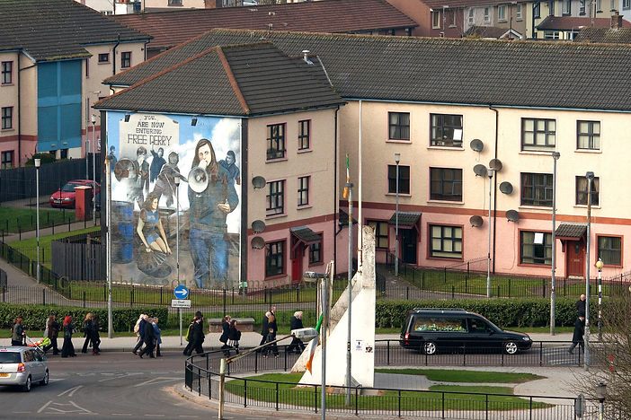 A Derry funeral procession passes 'Bernadette' - The Bogside Artists
