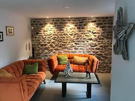Salon cosy du Gîte Amélie des Vosges, ouvert sur la salle de vie et vue sur la terrasse et le jardin