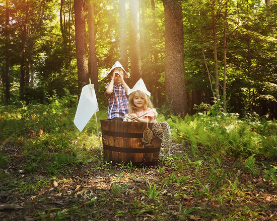 A little boy and girl are pretending to fish in a wooden barrel boat in the nature woods with a real