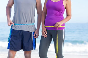 Couple-measuring-their-waist-481639230_3