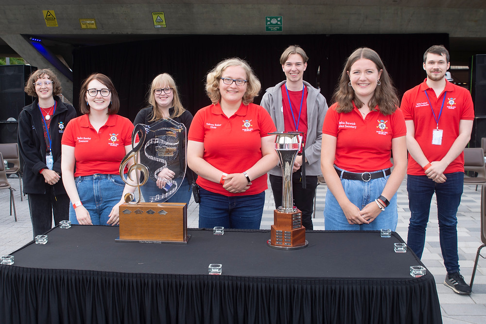 The 2021 UniBrass Organising Committee stand in front of a table with the UniBrass Trophy and Shield