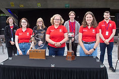 Photo of committee members behind the UniBrass trophy and shield