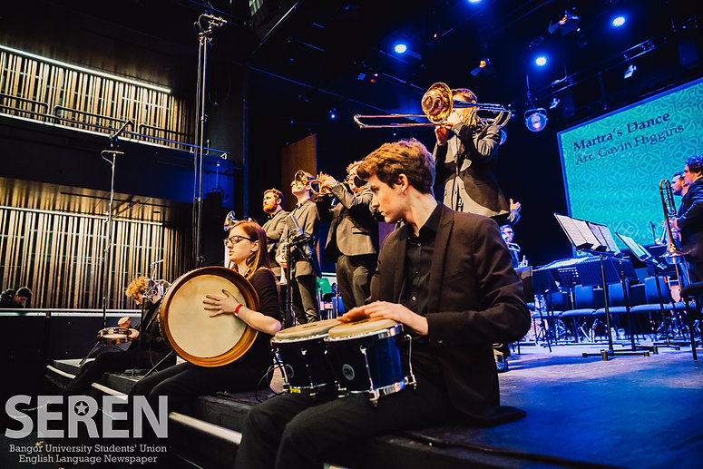 Performance of Matras Dance with percussionists playing a Bodhran at edge of stage