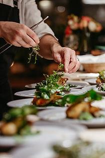 Chef hands garnishing plates