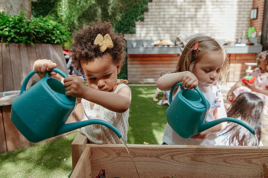 Two children watering plants in nursery