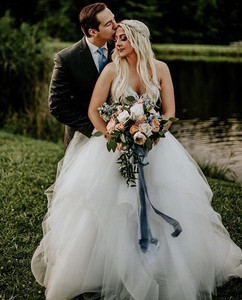 Evaline's Bride wearing her Hayley Paige ballgown with a bouquet and hair vine alongside her husband.