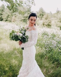 Evaline's Bride wearing her Calla Blanche fitted wedding gown from Evaline's Bridal surrounded by soft flowers