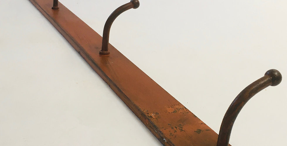 Vintage industrial metal bar of coat hooks with old worn orange paint