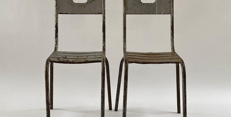 A pair of French vintage industrial metal chairs with a tubularframe and slat-style seat