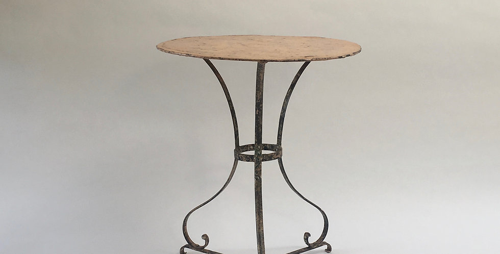 Vintage French bistro table in a shade of peach, with shapely wrought iron legs and a lovely patina