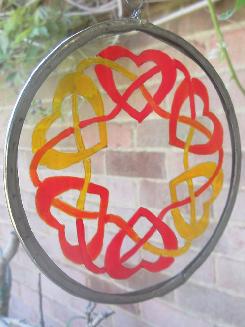 Celtic hearts entwined by threads in red, orange and yellow - small suncatcher