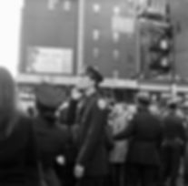 NY City policeman on phone with crowd