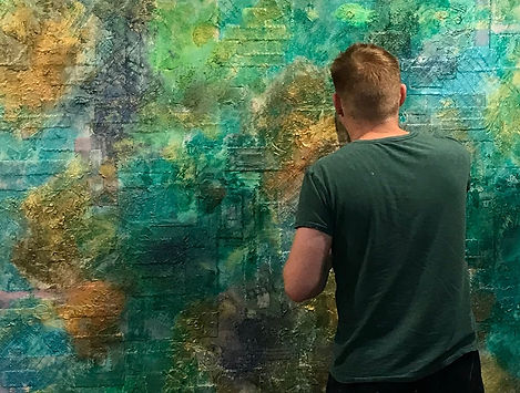 Artist at work with large abstract mixed media piece