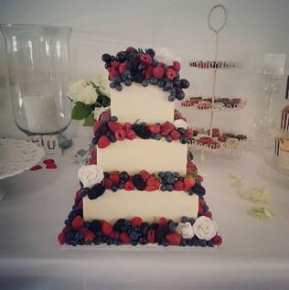 Yummy white chocolate iced wedding cake covered in so many fresh berries! #yum #cakeladycakes #berriescake #weddingcake