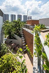 """The Breathing house dành cho một gia đình độc thân, tọa lạc tại trung tâm Thành phố Hồ Chí Minh. Lô đất rộng 3,9m, sâu 17,8m, chỉ vào được bằng con hẻm nhỏ xung quanh đông đúc. Trong khu phố có mật độ dân số cực cao này, chúng tôi muốn thiết kế một ngôi nhà vừa giới thiệu môi trường bên ngoài vừa đảm bảo sự riêng tư. Do hoàn cảnh của địa điểm, việc mở cửa của tòa nhà bị hạn chế về mặt vật lý đối với mặt trước, mặt trên và mặt sau của ngôi nhà. Để điều chỉnh khoảng cách giữa các tòa nhà lân cận trong khi tối đa hóa diện tích mở cửa, chúng tôi đã bao bọc ba bề mặt của tòa nhà nói trên bằng một """"tấm màn xanh"""", được làm bằng các loại cây leo mọc trên lưới thép. Lớp mềm này, như một bộ khuếch tán môi trường, lọc ánh nắng trực tiếp và ngăn không gian bên trong tiếp xúc quá nhiều với bên ngoài, không có cảm giác bị cô lập. Nó bao gồm các hộp trồng cây ở mỗi tấm sàn, với các phần tử thép mạ kẽm mô-đun hóa được gắn vào nó. Cấu trúc này mang đến một tầm nhìn xanh mát khắp ngôi nhà, đồng thời bảo vệ người dân khỏi tội phạm đô thị.  Bên trong """"bức màn xanh"""", tòa nhà bao gồm 5 khối tháp giống như tháp được xếp so le và kết nối với nhau, được bố trí ở giữa hai bức tường ranh giới. Các không gian bên ngoài được tạo ra bởi sự sắp xếp so le của các khối, mà chúng tôi gọi là """"Microvoids"""", đóng vai trò cung cấp vô số các tuyến chiếu sáng và thông gió gián tiếp trong toàn bộ tòa nhà. Trong khu đất hẹp và sâu được hàng xóm bịt kín cả hai bên, việc tăng cường thông gió cho từng góc của ngôi nhà sẽ hiệu quả hơn về mặt môi trường, bằng nhiều """"lỗ nhỏ"""", thay vì chỉ có một sân lớn. Các """"microvoids"""" có các lỗ mở trên mỗi tầng, qua đó cư dân có tầm nhìn xuyên suốt theo chiều dọc và chéo hơn từ mọi nơi, nhìn vào không gian xanh và các không gian khác. Cầu thang cũng được thiết kế là một trong những ô thoáng lấy ánh sáng từ trên xuống và các lỗ thoáng hướng ra các phòng. Thành phần xốp của tòa nhà làm giảm việc sử dụng điều hòa không khí để tăng cường thông gió tự nhiên, tạo ra sự kết nối không g"""