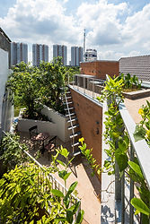 """The Breathing house is for a single family, located in the heart of Ho Chi Minh City. The plot is 3.9m wide and 17.8m deep, only accessible by a tiny alley with crowded surroundings. Within this extremely high-dense neighborhood, we aimed to design a house that introduces an external environment while ensuring privacy.  Due to the circumstances of the site, the opening of the building was physically constrained to the front, top and back of the house. In order to adjust the distance between neighboring buildings while maximizing the opening area, we wrapped the aforementioned three surfaces of the building with a """"green veil"""", which is made of creeper plants that grow on a steel mesh. This soft layer, as an environmental diffuser, filters direct sunlight and prevents the interior space from overexposure to the outside, without the feeling of isolation. It is composed of planter boxes at each floor slab, with modularized galvanized steel elements attached to it. This structure provides a green view throughout the house, which also protects the residents from urban crime.  Inside the """"green veil"""", the building consists of 5 tower-like volumes that are staggered and connected to each other, arranged in between the two boundary walls. The external spaces created by the staggered arrangement of the volumes, which we call """"Microvoids"""", play a role in providing myriad indirect lighting and ventilation routes throughout the building. In the narrow and deep plot shuttered by neighbors on both sides, it is more environmentally effective to promote ventilation for each corner of the house, by multiple """"microvoids"""", rather than having a singular large courtyard. The """"microvoids"""" have openings on each of the floors, through which the residents have a more longitudinal and diagonal see-through view from everywhere, looking into the green and other spaces. The staircase is also designed as one of the microvoids with top light and openings facing the rooms. The porous composition o"""