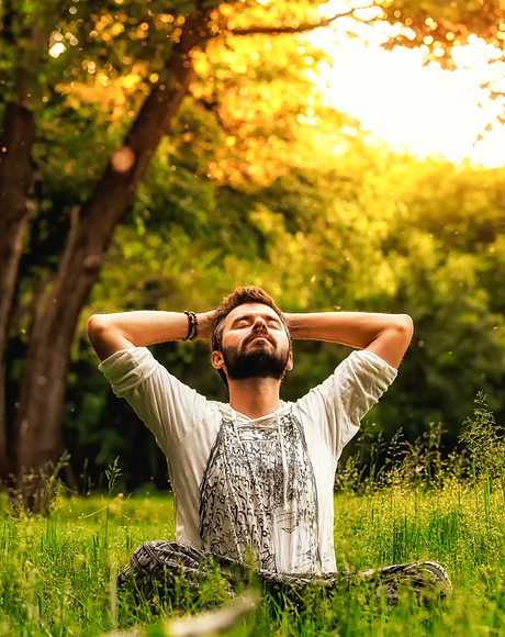 A man sitting on grass in the park and stretching with eyes closed and hands behind head_edited.png