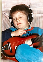 Kid playing guitar and listening to music