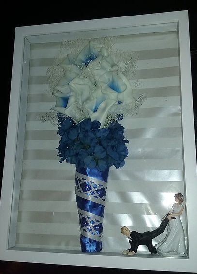 A bride's faux bouquet and cake topper diplayed in a shadowbox.