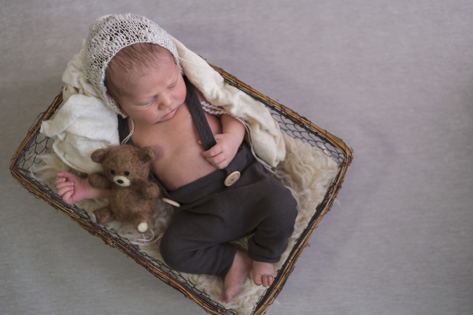 newborn boy sleeps in basket photo