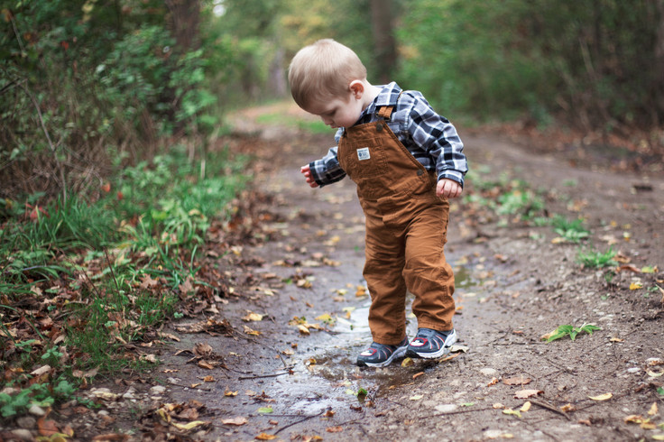 toddler boy splashing in the forest