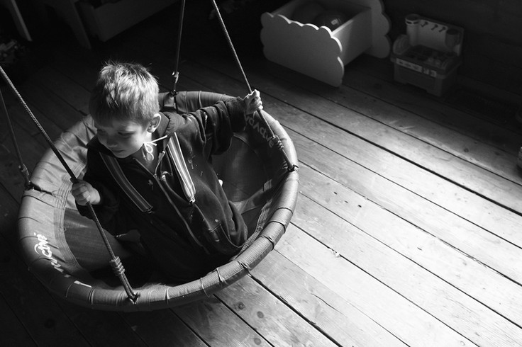 Boy swings in his bedroom wearing dads sweater