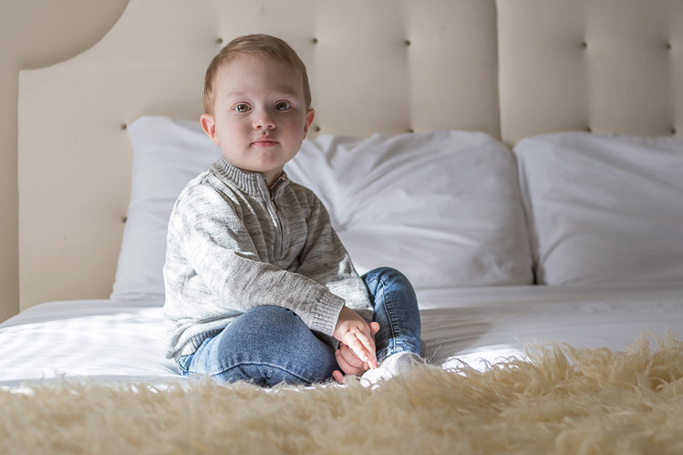 boy sits on bed lifestyle photography