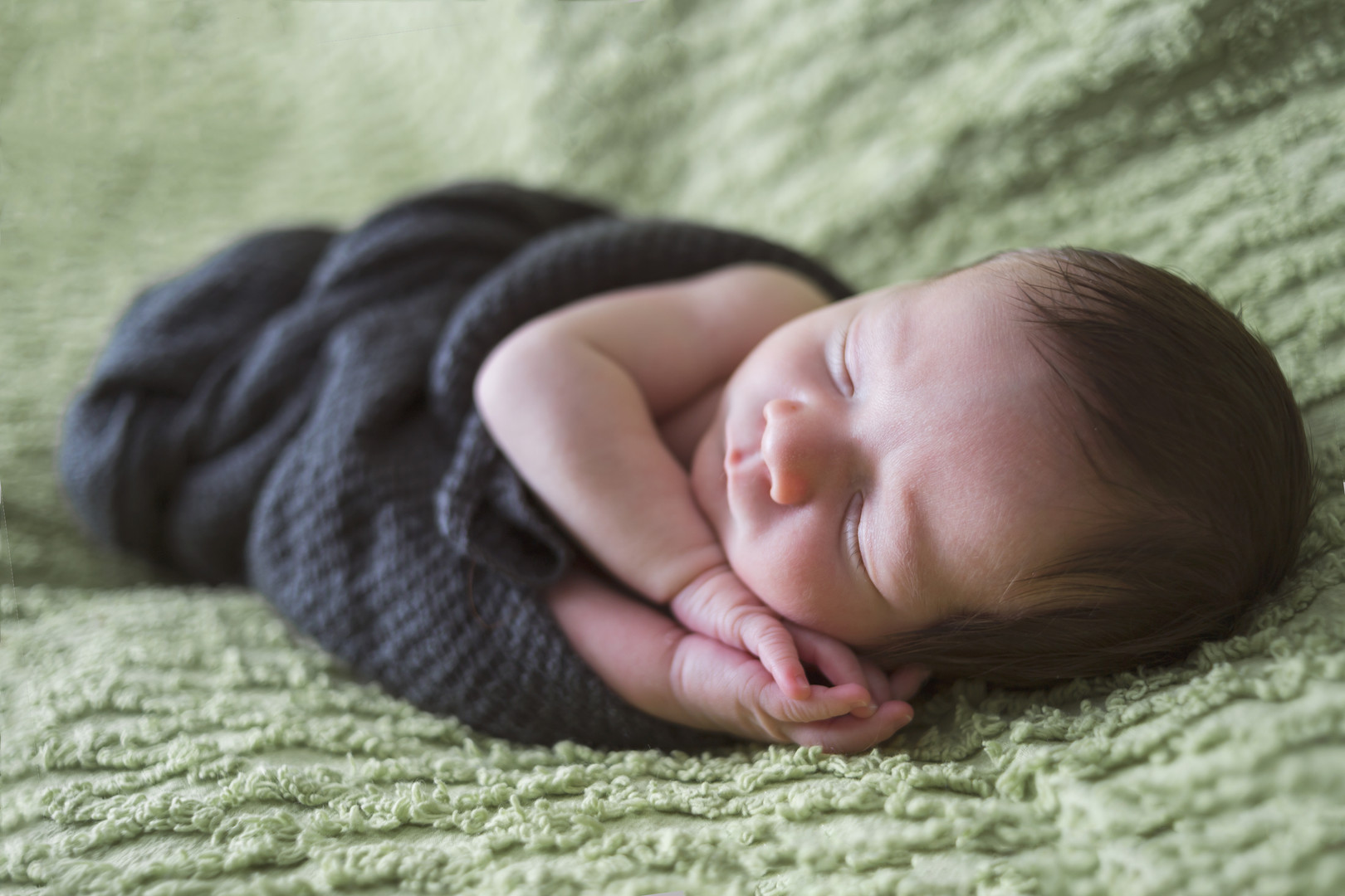 sleepy newborn boy on textured fabric