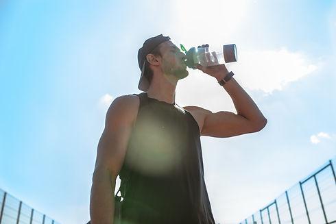 Muscular-sportsman-drinking-water-562375