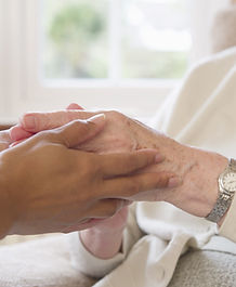 Hands holding an elderly person's hands