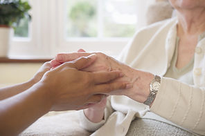 A youger person holding onto the hands of an older person.