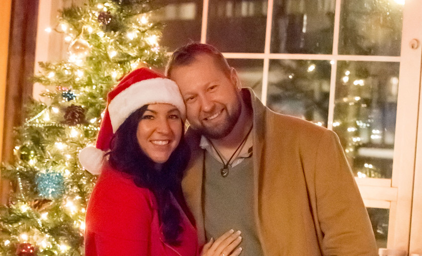 A couple posing by the Christmas tree.