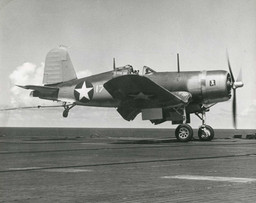 """F4U-1 Corsair of VF-17, """"The Jolly Rogers,"""" landing aboard the carrier Bunker Hill"""