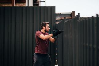 Industrial construction handyman using screwdriver for installing fence.jpg