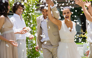 couple with guests throwing rose petals