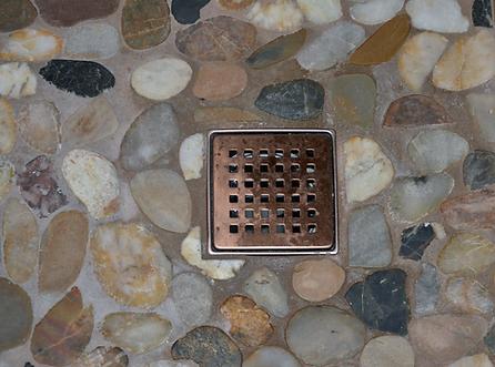 bronze drain, river rock, natural stone