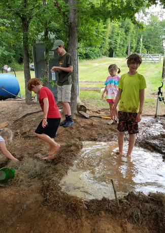 Christian playing in mud hole at camp.jp