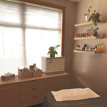 Looking into the salon and showing the massage table and natural products on shelves