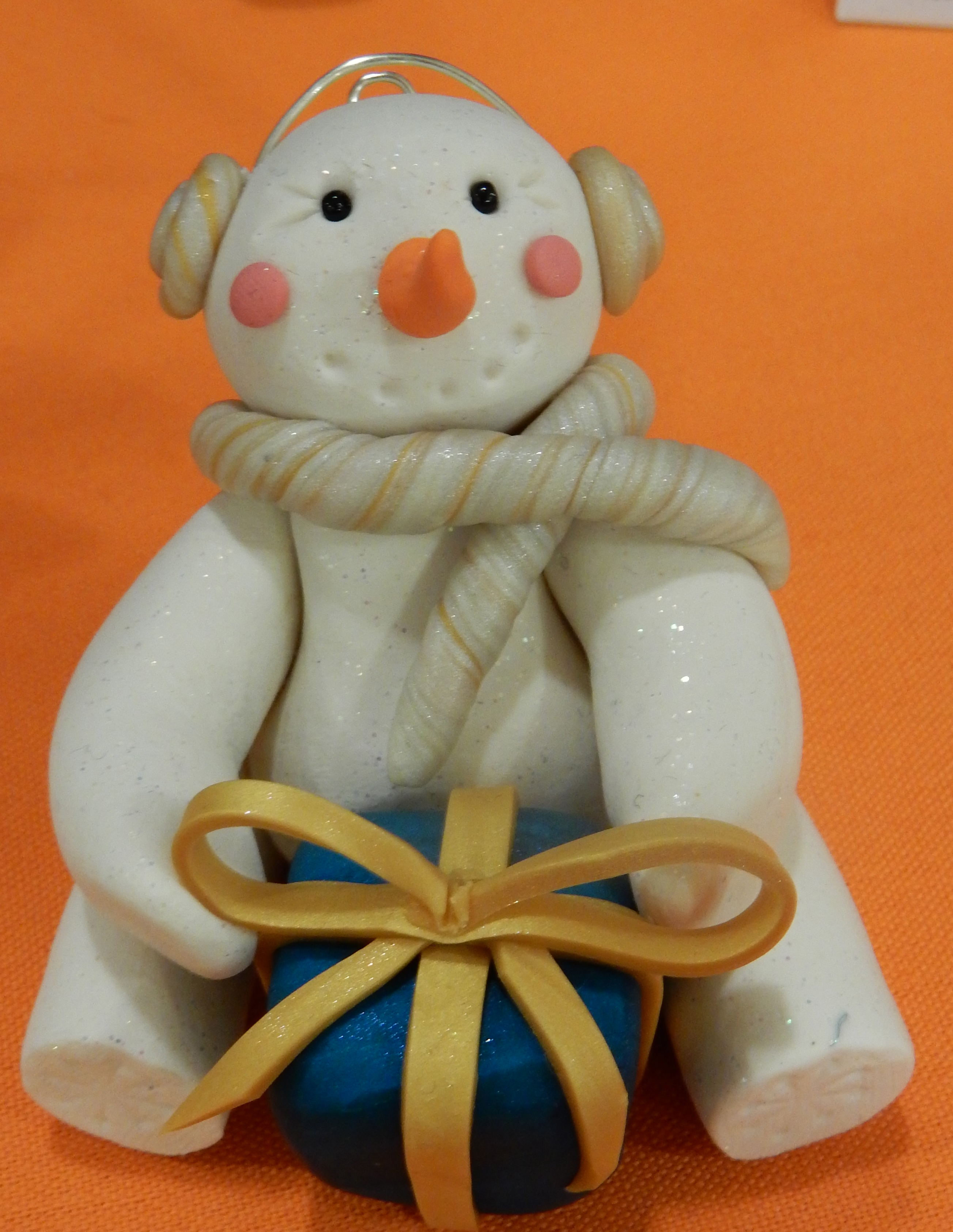 snowman with blue present and scarf