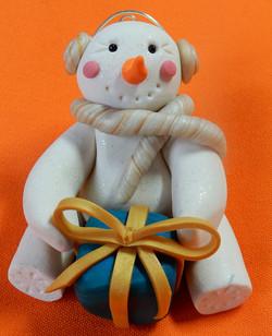 snowman blue present gold ribbon ear muffs and scarf