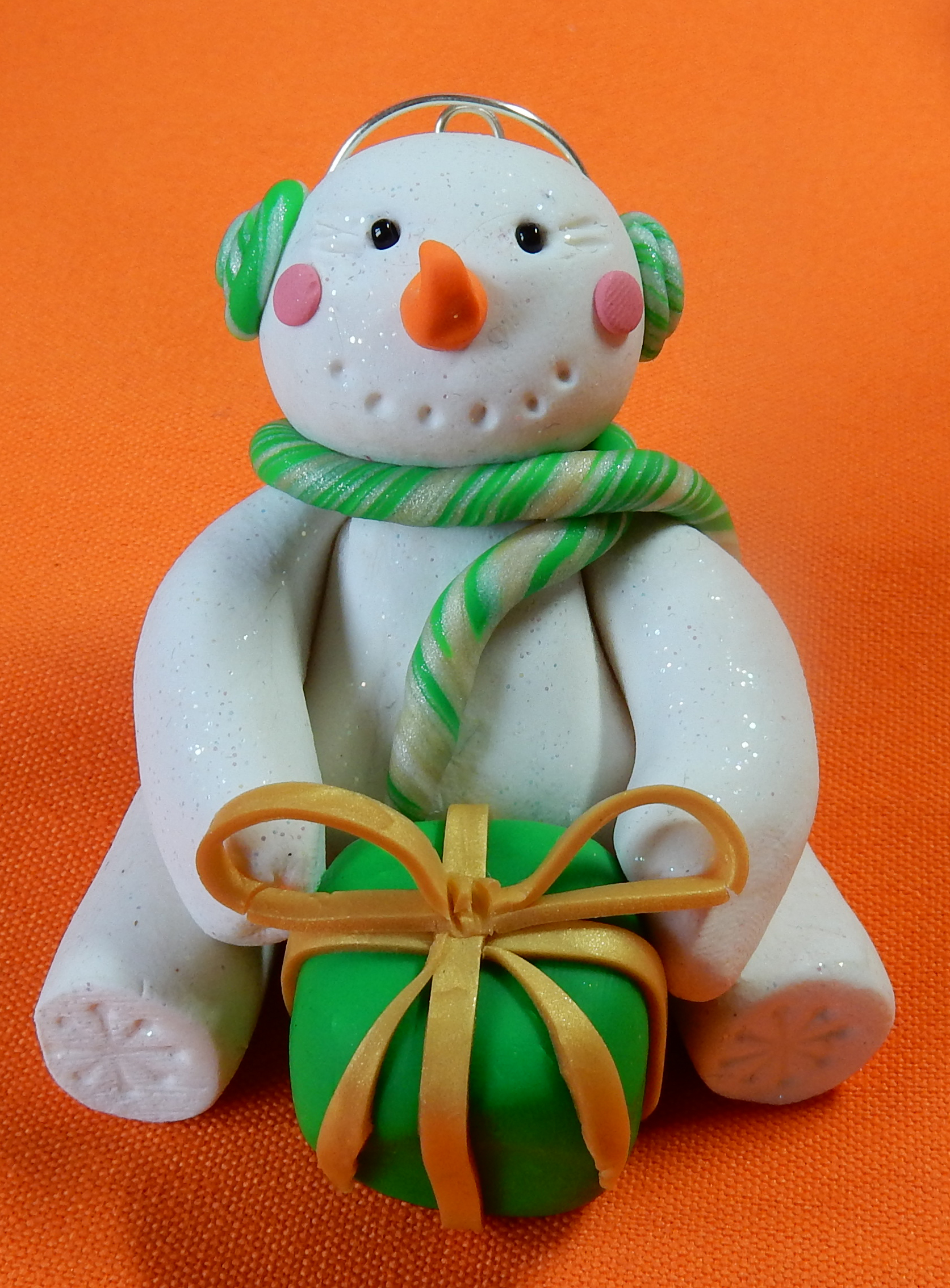 snowman with green present ear muffs and scarf