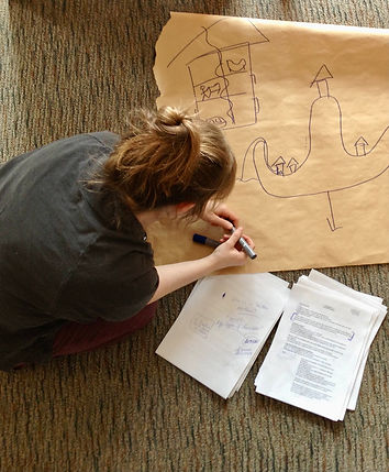 a person writing on big paper with a marker while working on a script project