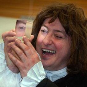 David Hall as Sir Isaac Newton peeping through his prism