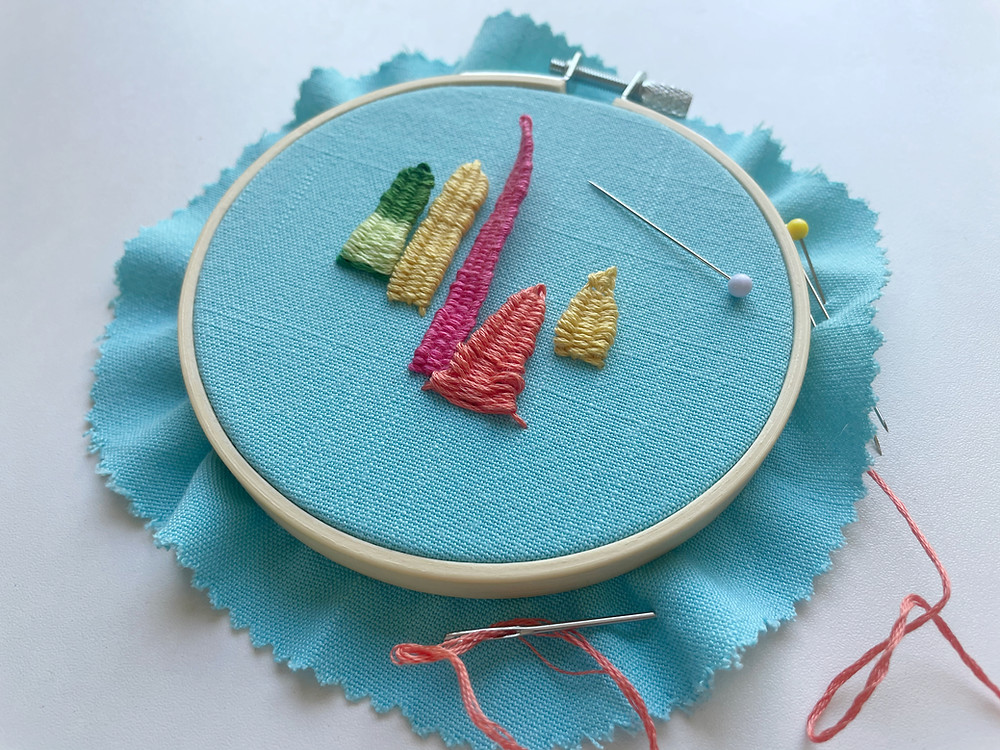 An embroidery hoop with 3D leaves stitched in green, yellow, pink, and orange onto bright blue fabric.