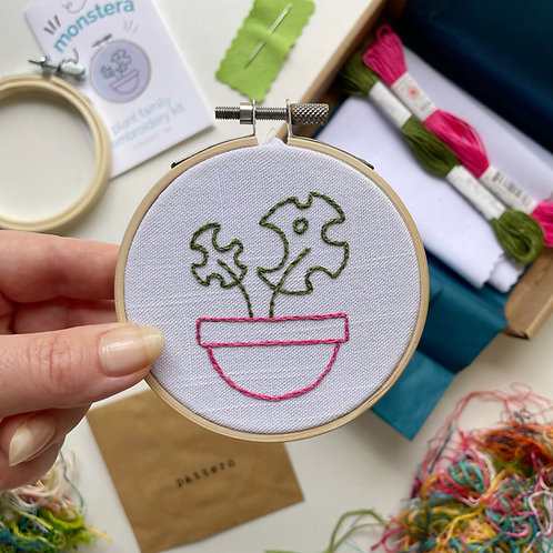 Photo of an embroidery hoop with a green monstera plant in a pink planter on white fabric.