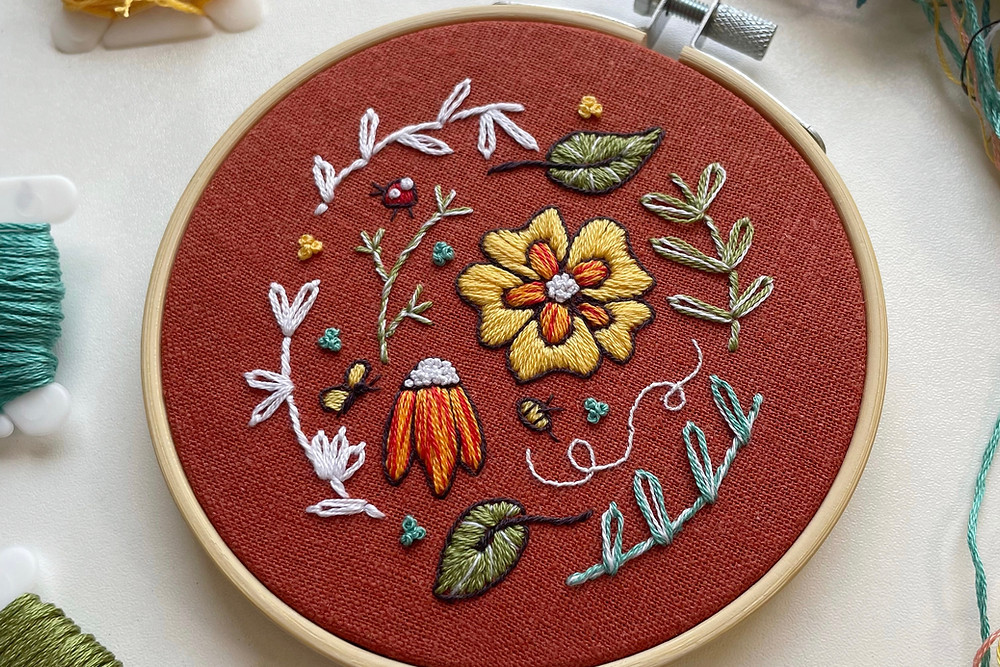 Photo of an embroidery hoop with a floral sampler stitched in yellow, red, white, blue, and green onto dark orange fabric.
