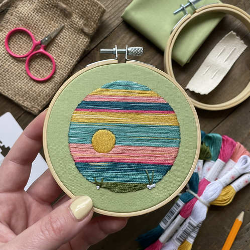 Hope holds up an embroidery hoop with a landscape stitched onto green fabric.