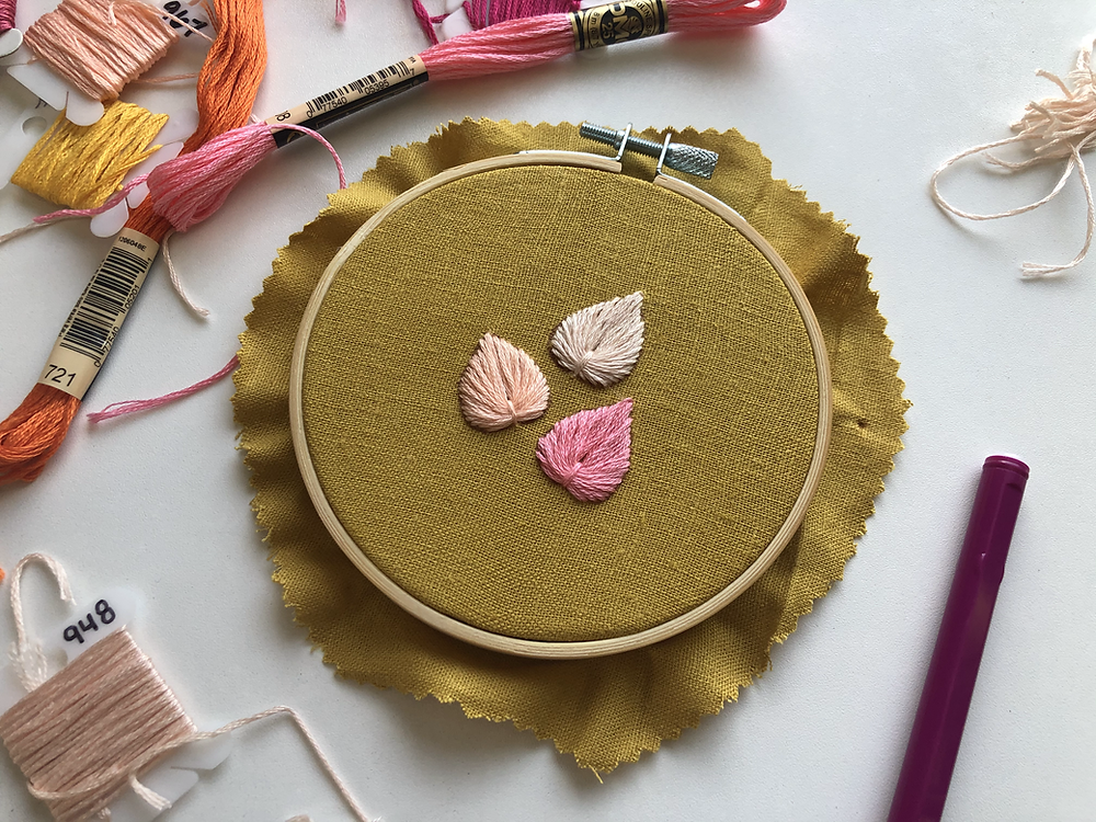 An embroidery hoop with three leaves stitched in different shades of pink onto mustard fabric sits on a white background, surrounded by a purple pin and different colors of embroidery floss.