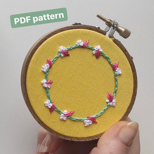 """An embroidered wreath in green, pink, and white, on bright yellow fabric; text reads, """"PDF pattern"""""""