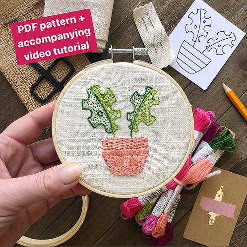 A picture of an embroidery hoop with a potted monstera plant stitched in greens and pink onto white fabric.